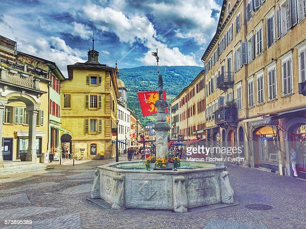 empty road along built structures - valais canton stock pictures, royalty-free photos & images