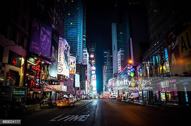 empty road along illuminated buildings - times square manhattan stock pictures, royalty-free photos & images