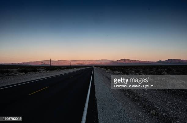 empty road along landscape against clear sky during sunset - christian soldatke stock pictures, royalty-free photos & images