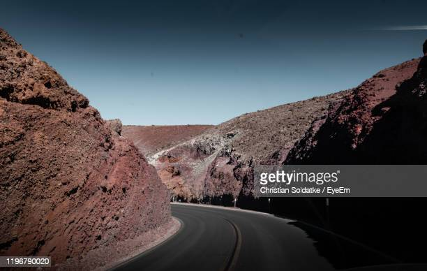 empty road along landscape against clear sky - christian soldatke stock pictures, royalty-free photos & images