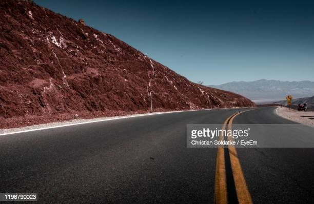 empty road along landscape against clear sky - christian soldatke foto e immagini stock