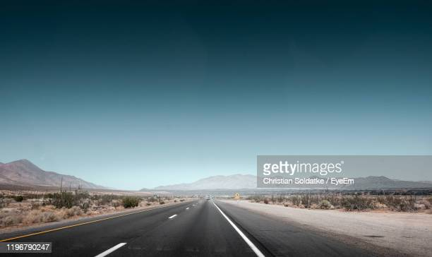 empty road along landscape against clear sky - christian soldatke imagens e fotografias de stock