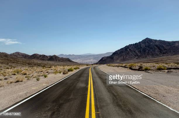 empty road along landscape and mountains against sky - double yellow line stock photos and pictures