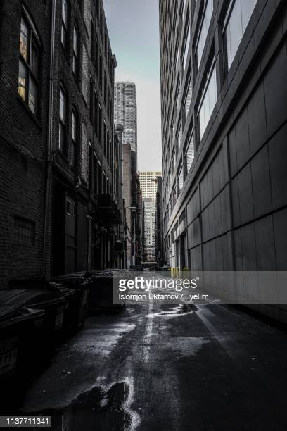 empty road amidst buildings against sky in city - alley stock photos and pictures