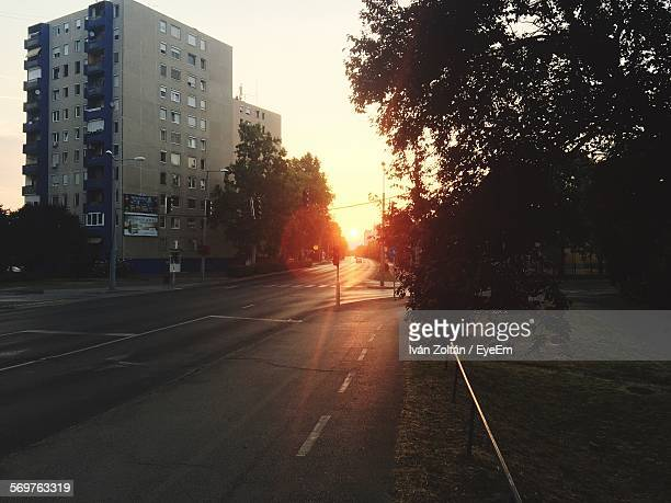 Empty Road Amidst Buildings And Trees Against Sky At Sunset