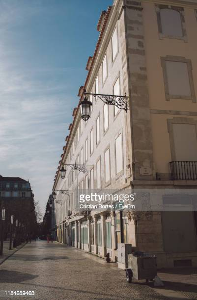 empty road amidst buildings in city against sky - bortes stock photos and pictures