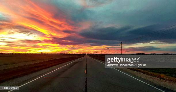 Empty Road Amidst Cloudy Sky At Sunset
