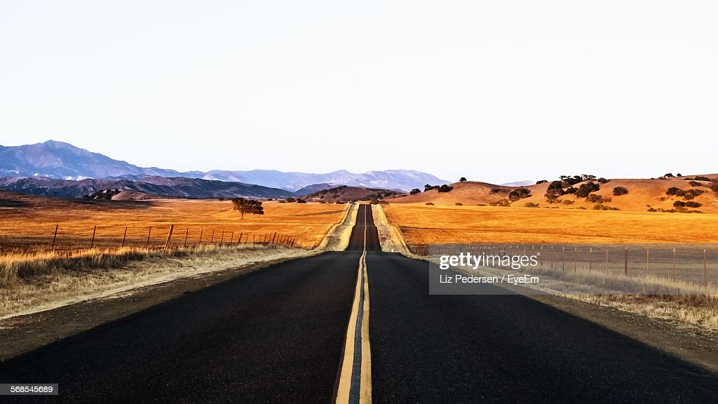 Empty Road Amidst Field Against Clear Sky : Stock Photo