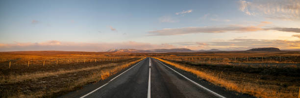 Empty road amidst field against sky during sunset,Iceland