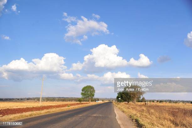 empty road amidst field against sky - jose ayala stock pictures, royalty-free photos & images