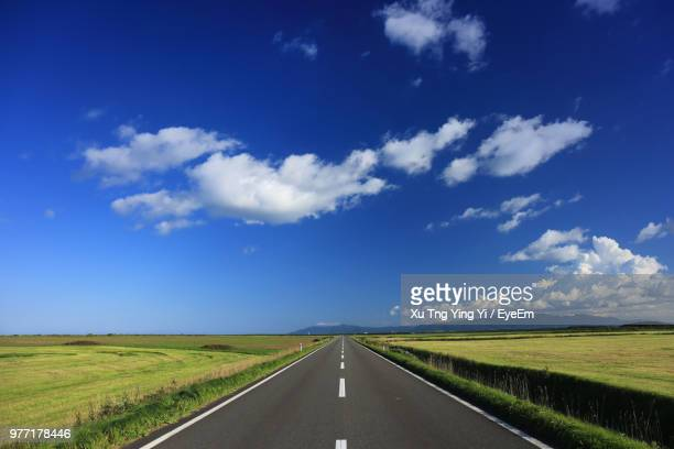 empty road amidst field against sky - 地平線 ストックフォトと画像