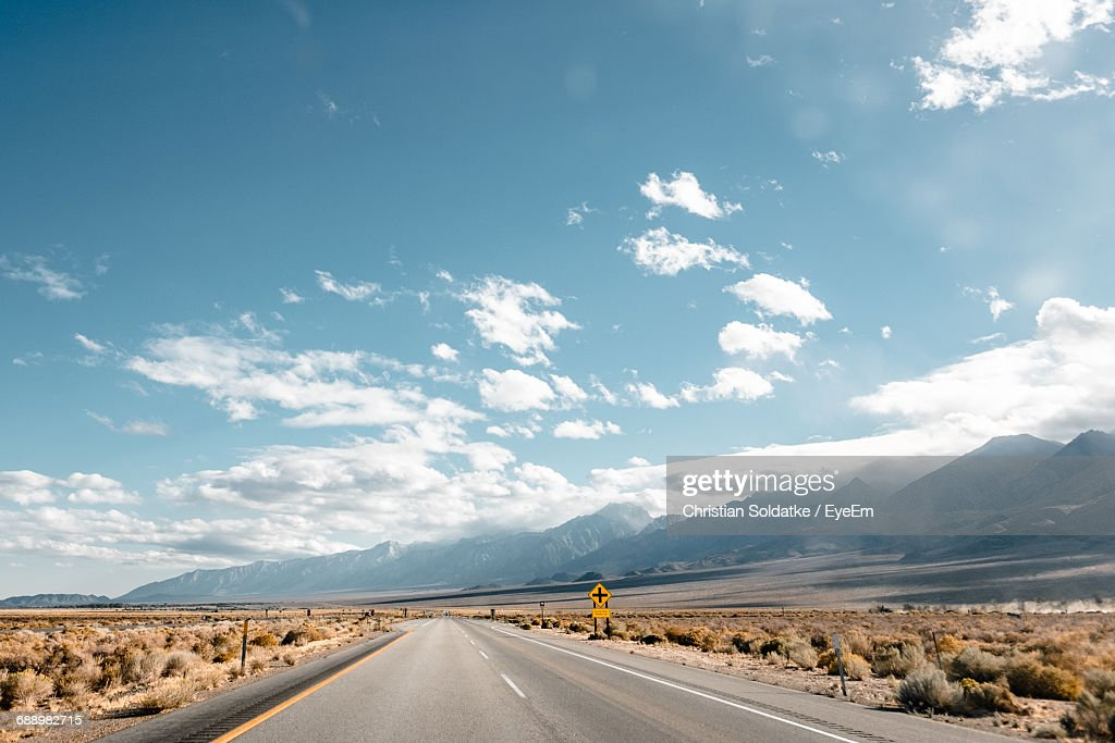 Empty Road Amidst Field By Mountain Against Sky : Stock-Foto