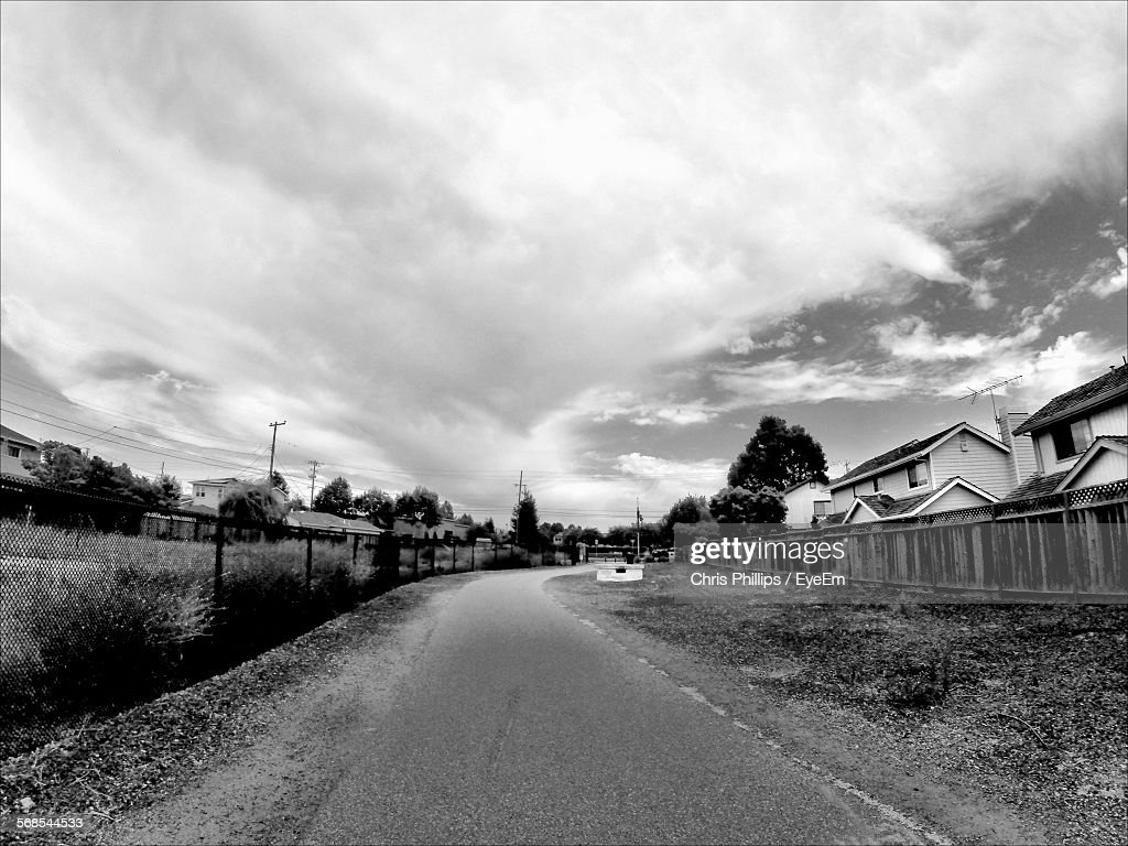 Empty Road Amidst Houses Against Cloudy Sky : Stock Photo