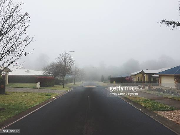 Empty Road Amidst Houses Against Sky During Foggy Weather