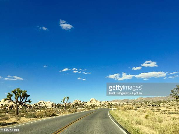 empty road amidst landscape against blue sky - san bernardino california stock pictures, royalty-free photos & images