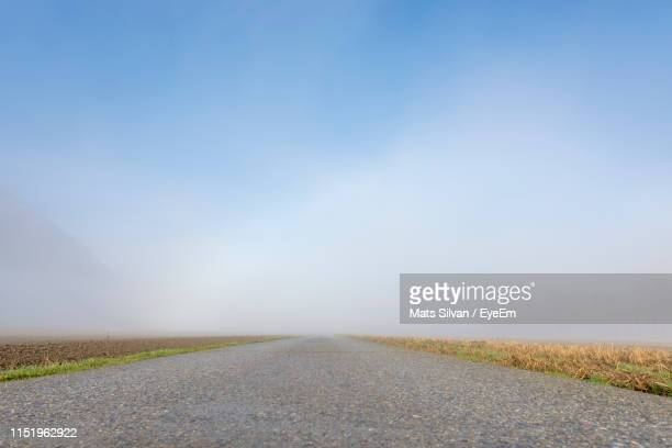 empty road amidst landscape against clear sky during foggy weather - kanton tessin stock-fotos und bilder