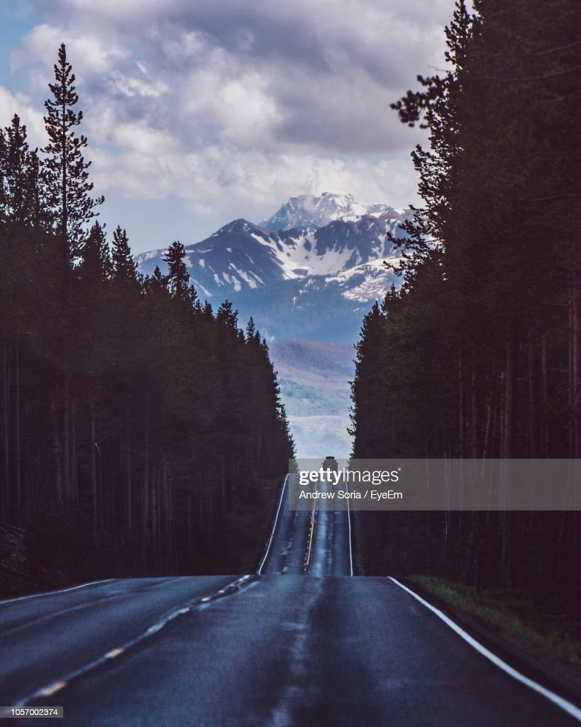 Empty Road Amidst Silhouette Trees Against Mountains : Stock Photo