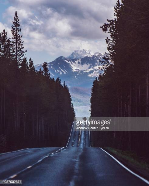 Empty Road Amidst Silhouette Trees Against Mountains