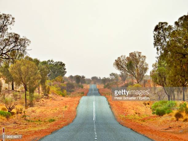 empty road amidst trees against clear sky - alice springs stock pictures, royalty-free photos & images