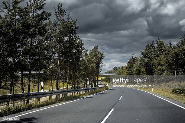 empty road amidst trees against cloudy sky - albrecht schlotter stock photos and pictures