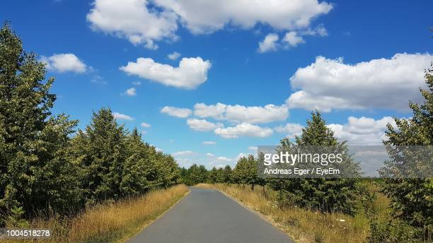 Empty Road Amidst Trees Against Sky