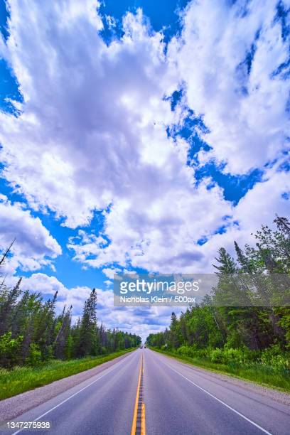 empty road amidst trees against sky - klein stock pictures, royalty-free photos & images