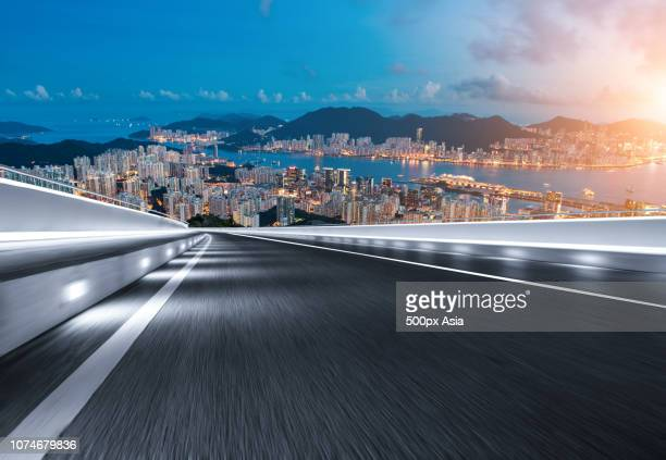 empty road and illuminated city in background, australia - image stock pictures, royalty-free photos & images