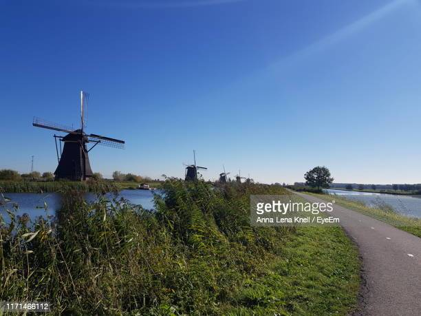 empty road and river against clear blue sky - netherlands stock pictures, royalty-free photos & images