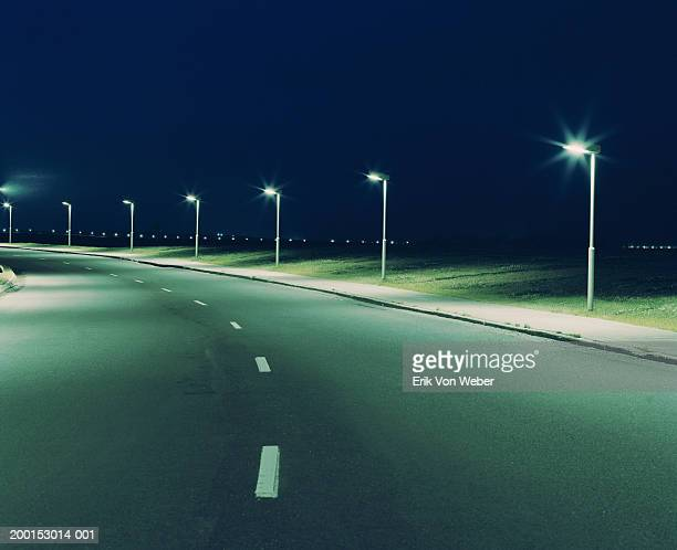 Empty road and streetlights at night