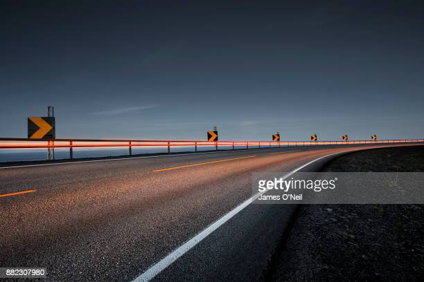 empty road at night with light trails - vehicle light stock photos and pictures