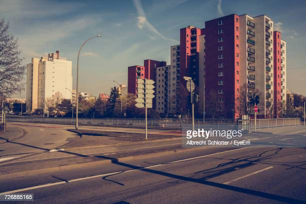 empty road by buildings in city against sky - albrecht schlotter stock photos and pictures