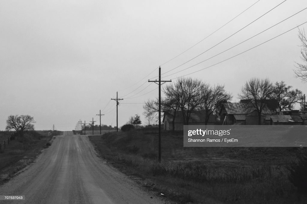 Empty Road By Electricity Pylons And Houses On Grassy Field Against ...