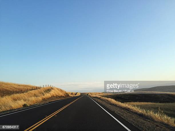 empty road by field against clear sky - baum stock pictures, royalty-free photos & images