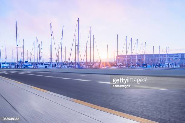 empty road by harbor with many yachts moored at