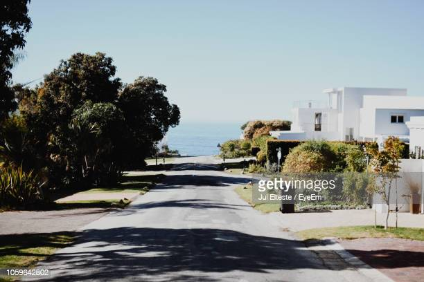 Empty Road By Houses Leading Towards Sea Against Clear Sky