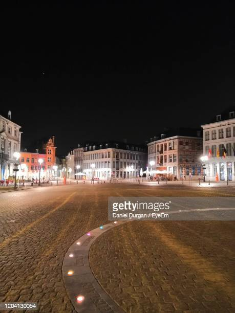 empty road by illuminated buildings against clear sky at night - hainaut stock pictures, royalty-free photos & images