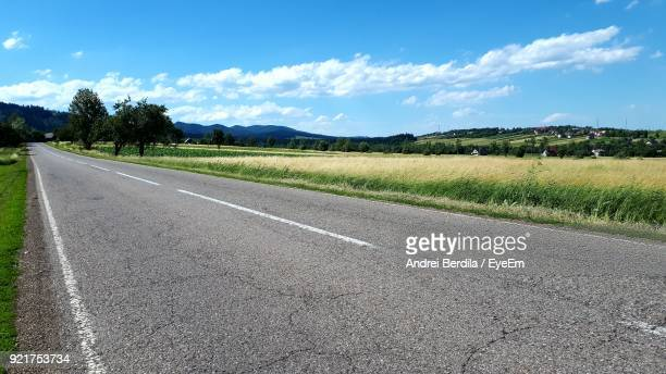 Empty Road By Landscape Against Sky