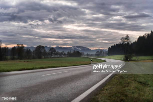 Empty Road By Landscape Against Storm Clouds