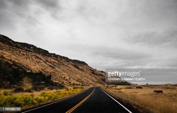 empty road by mountain against cloudy sky - christian soldatke stock pictures, royalty-free photos & images