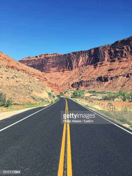 empty road by mountains against sky - double yellow line stock photos and pictures