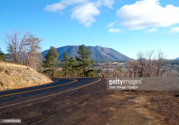 empty road by mountains against sky - flagstaff arizona stock pictures, royalty-free photos & images