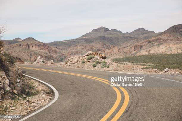 empty road by mountains against sky - bortes stock-fotos und bilder