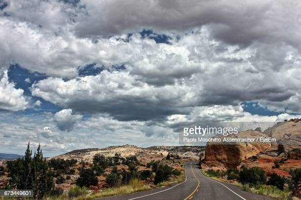 Empty Road By Rock Formations Against Cloudy Sky