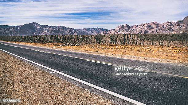 Empty Road By Rocky Mountains Against Sky