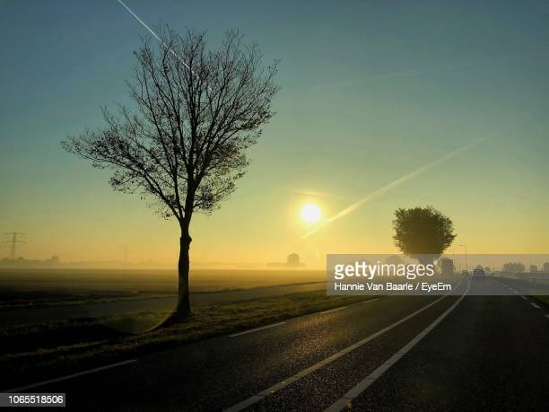 Empty Road By Trees On Field Against Sky At Sunset