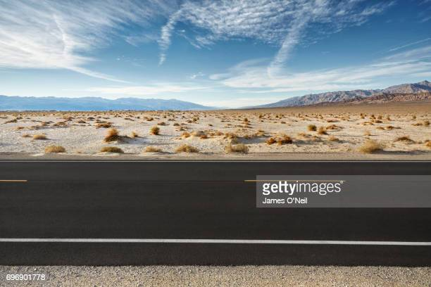 empty road in desert landscape with distant mountains - 境界線 ストックフォトと画像
