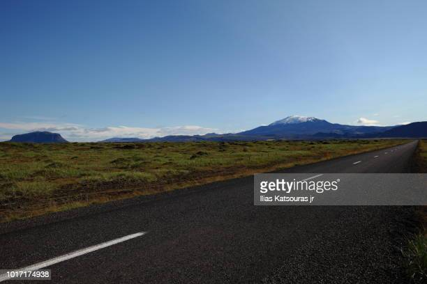 empty road in iceland, with mountains and volcano in the background - agosto fotografías e imágenes de stock