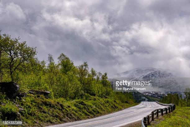empty road in northern norway - low skyes and fog - snowy mountains in the background - finn bjurvoll stock-fotos und bilder