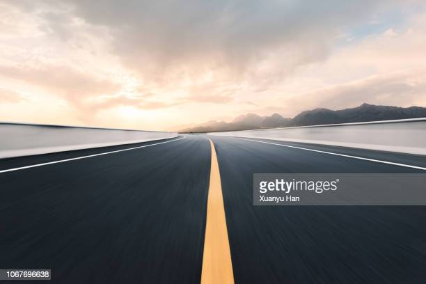 empty road leading to mountain range - dividing line road marking stock pictures, royalty-free photos & images