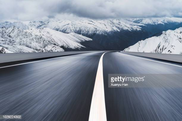 Empty road leading to snow covered mountains